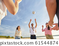 friends playing volleyball on beach in summer 61544874