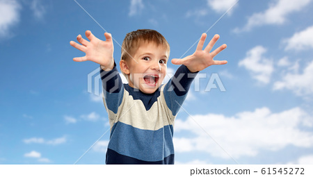 little boy making scary faces over sky background 61545272