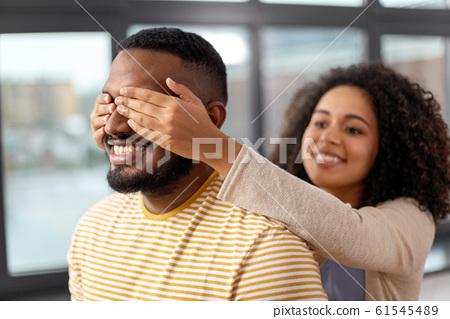 happy african american woman closing man's eyes 61545489