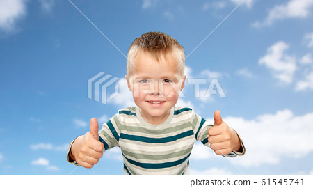smiling boy in striped shirt showing thumbs up 61545741