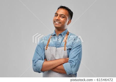 smiling indian barman, waiter or salesman in apron 61546472
