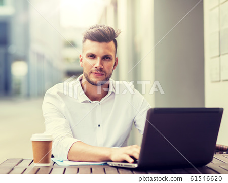 man with laptop and coffee at city cafe 61546620