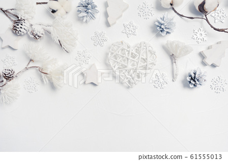 Design elements Christmas greeting card with Xmas gift box, cones, cotton flowers, heart, snowflakes with place for your text. Decorations on a white wooden background 61555013