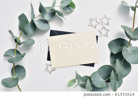 Mock up of Eucalyptus leaves and decor of stars paper clip with place for text on white background. Wreath made of eucalyptus branches. Flat lay, top view 61555014