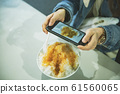 Woman holding smartphone to photograph ice cream 61560065