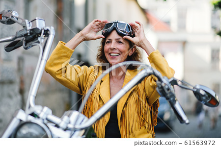 Cheerful senior woman traveller with motorbike in town. 61563972