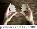 woman hand holding broken heart paper cut on wooden background 61572005