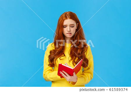 Perplexed and uneasy, concerned cute redhead female student having troubles with schedule, frowning reading girlfriend diary, feeling guilty, holding red notebook, feeling troubled, blue background 61589374