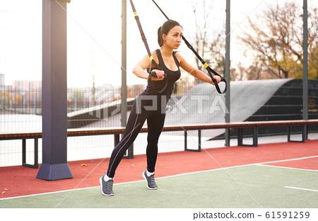 Girl athlete functional training on sportground. 61591259