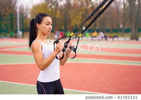 Girl athlete functional training on sportground. 61591331