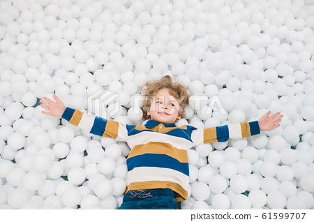 Cute little boy in casualwear outstretching his arms among white balloons 61599707