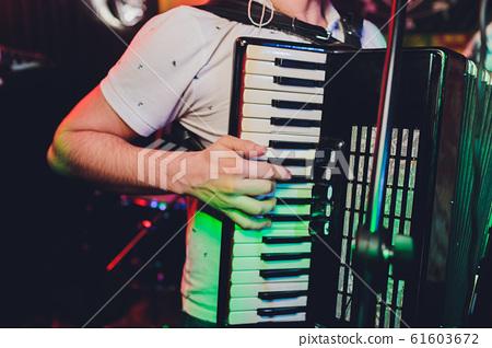 Image of musician playing on accordion closeup. 61603672