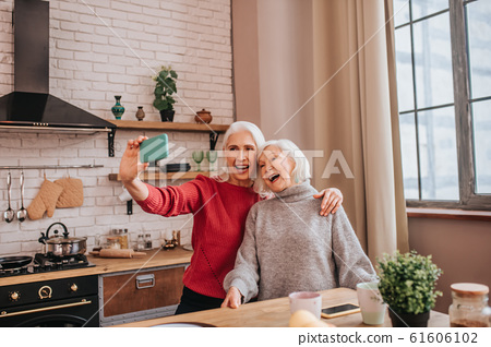 Two energetic grey-haired positive ladies looking happy 61606102