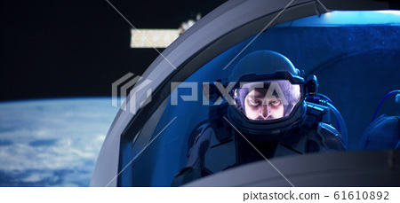 Astronaut looking out of spaceship window 61610892
