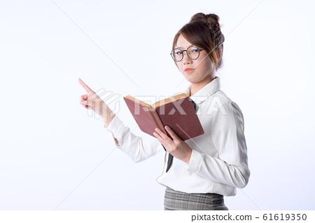 可愛的亞洲女孩穿白襯衫拿書用手指東西 61619350