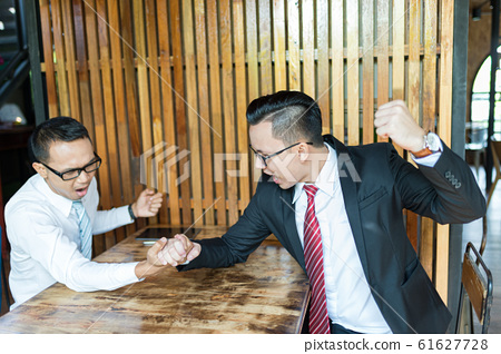 two businessman expressed a serious expression and fighting by used arm wrestling on wood table. one man win and one man defeated, concept of business competition 61627728