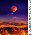 Moon eclipse. Night sky with blood moon above the fire is burning in the meadow. 61627952
