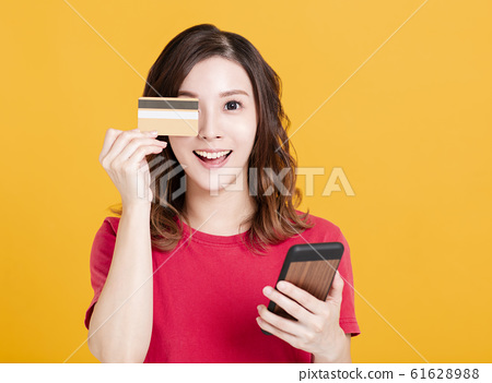 happy young woman holding smart phone and credit 61628988