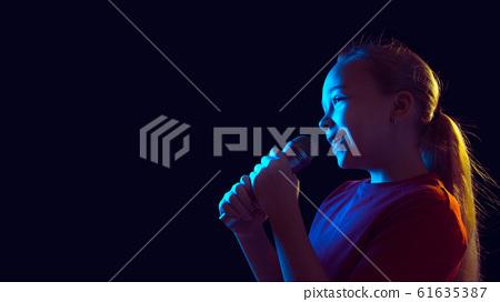 Caucasian girl's portrait isolated on dark studio background in neon light 61635387