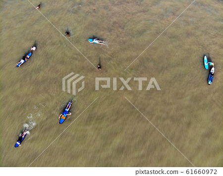 Aerial view of surfers waiting the waves in the dark, brown water in Bali, Indonesia 61660972