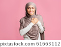 Grateful muslim girl keeping both palms on chest, expressing appreciation 61663112