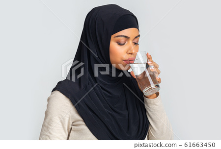 Black islamic girl in hijab drinking water from glass in studio 61663450