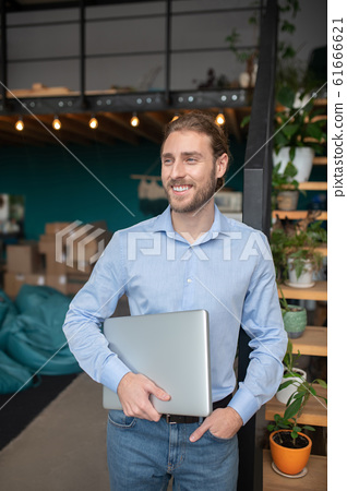 Smiling handsome man confidently holding his computer 61666621