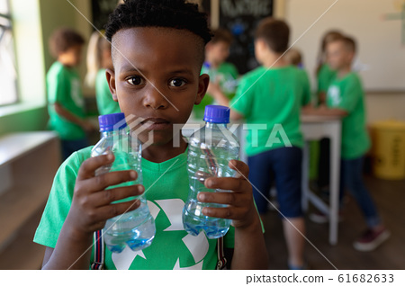 Schoolboy wearing a green t shirt with a white recycling logo on it and holding two plastic water bo 61682633