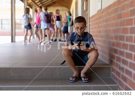 Schoolboy sitting on a step in the schoolyard at elementary school 61682682