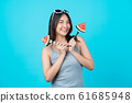 Portrait Attractive Asian young woman holding two Piece slide of watermelon and wearing fashion sunglasses on isolated blue color background, copy space and studio, diet and healthy fruit concept 61685948