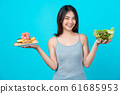 Attractive Asian young woman holding and choosing between disk of donuts or vegetable salad in glasses bowl on isolated blue color background, weight loss and avoid junk food for dieting and Healthy 61685953