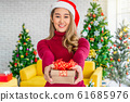 Portrait happiness asian woman wearing colorful red sweaters with hat holding and giving the gift box to other for merry christmas celebration, asian or asean indoors party, xmas and new year concept 61685976