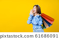 Attractive Asian smiling young woman Carrying a shopping coloful bag on aisolated yellow color background, copy space and studio, black friday season sale concept. 61686091