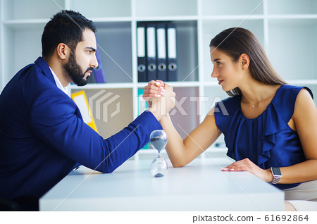 Side view portrait of man and woman armwrestling, exerting pressure on each other, looking eyes in eyes, struggling for leadership. Business, society concept photo 61692864