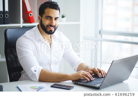 Young handsome entrepreneur sitting at desk and using laptop in office. 61696259