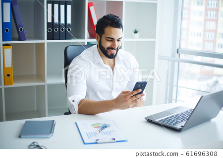 Young handsome entrepreneur sitting at desk and using laptop in office. 61696308