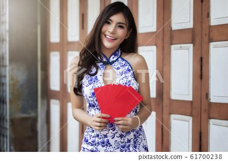 Chinese woman in cheongsam (qipao) dress holding red envelopes (hong bao) at shrine. 61700238