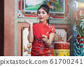 Chinese woman in a red cheongsam (qipao) dress holding red envelopes (hong bao) at shrine. 61700241