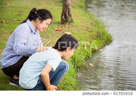 Asian little child girl about to throw up,vomit,puke retch barf,feeling sick from indigestion or food poisoning,stomach upset virus,cute daughter with woman or mother helping,care her in outdoor park, 61701019
