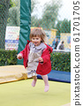 Little girl on playground in a park, jumping 61701705