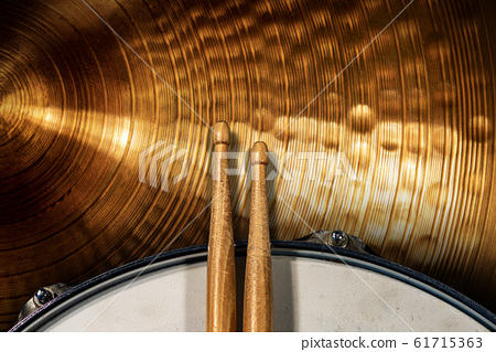 Two wooden drumsticks on a snare drum and golden cymbal - Percussion instrument 61715363