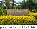 AGIA NAPA, CYPRUS - MAY 26, 2019: the Nissi Beach Resort Hotel signboard, Ayia Napa.This sign is set in the bushes, on the background of palm trees. 61717660