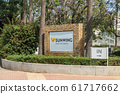 AGIA NAPA, CYPRUS - MAY 26, 2019: the Sunwing Sandy Bay Beach Hotel signboard, Ayia Napa. This sign is set in the bushes, on the background of palm trees. 61717662