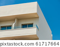 Modern new building with open balconies against the summer blue sky 61717664