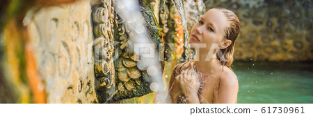 Young woman in hot springs banjar. Thermal water is released from the mouth of statues at a hot 61730961