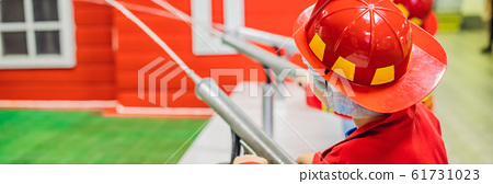 Expressive cute toddler with fireman's outfit playing fireman BANNER, LONG FORMAT 61731023