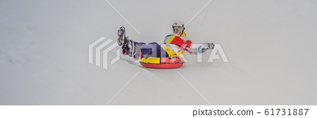 man snow tubing from hill. winter activity concept BANNER, LONG FORMAT 61731887