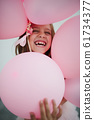 portait of happy young girl with pink balloons 61734377
