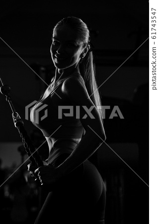 pretty caucasian fitness woman pumping up muscles 61743547