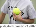 Person holding tennis balls on tennis court 61745887